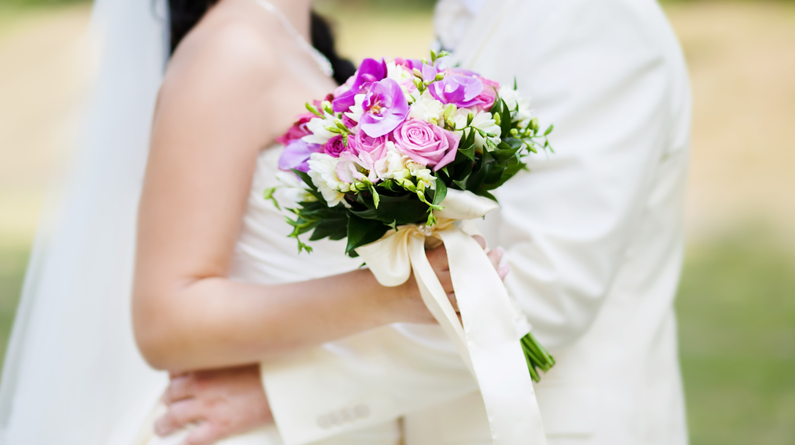 Bride standing with her groom with a bouquet of flowers in her hand